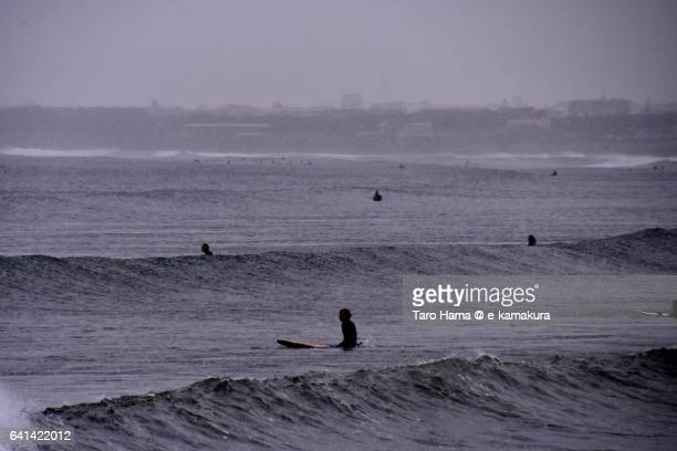 A surfer waiting for next wave on the snowing beach