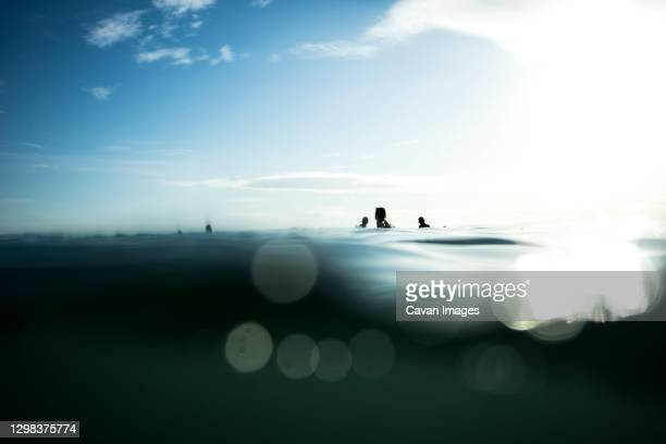 surfer waiting for the series with the calm sea - waiting stock pictures, royalty-free photos & images