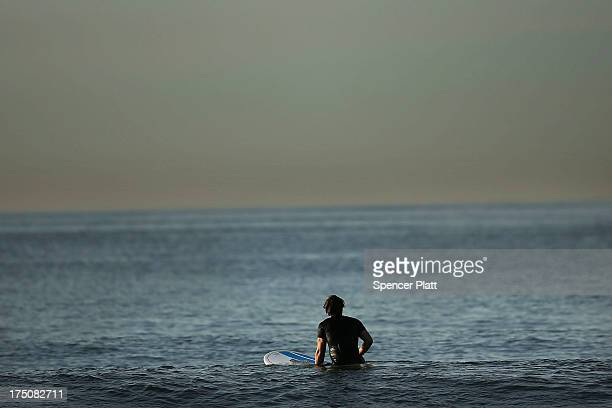 Surfer waits for a wave during an early morning surfing session at Rockaway Beach on July 31, 2013 in the Queens borough of New York City. Despite...