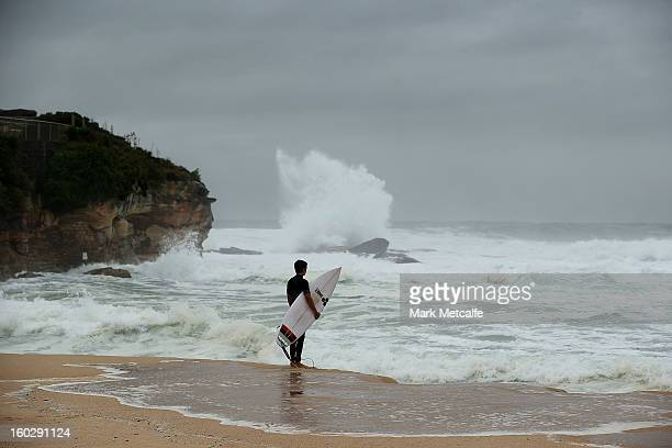 A surfer waits to jump in to the ocean during stormy conditions at Coogee Beach after winds and rain battered Sydney last night on January 29 2013 in...