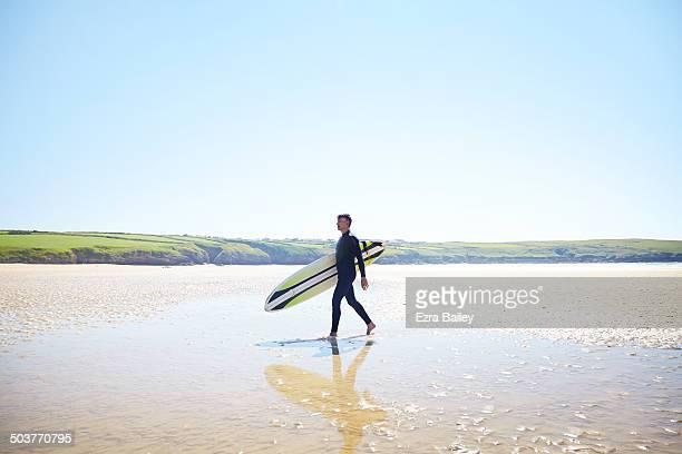 Surfer walking along deserted beach.