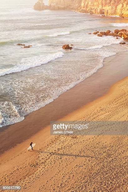surfer walking along shoreline on beach shot from above, sagres, portugal - sagres stock pictures, royalty-free photos & images