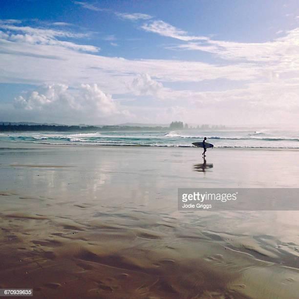Surfer walking down the beach