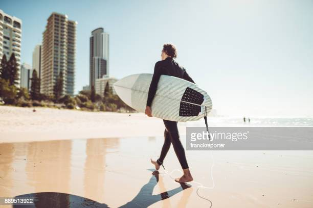 surfer walking in surfers paradise beach in australia - gold coast queensland stock pictures, royalty-free photos & images