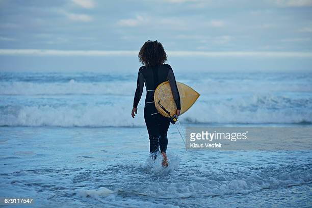 Surfer walking into the waves with board