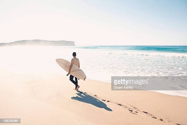 Surfer walking on beach with surfboard