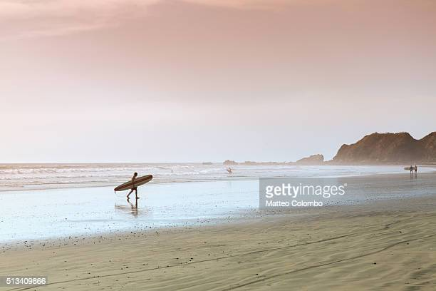 surfer walking on the beach at sunset, costa rica - guanacaste stock pictures, royalty-free photos & images