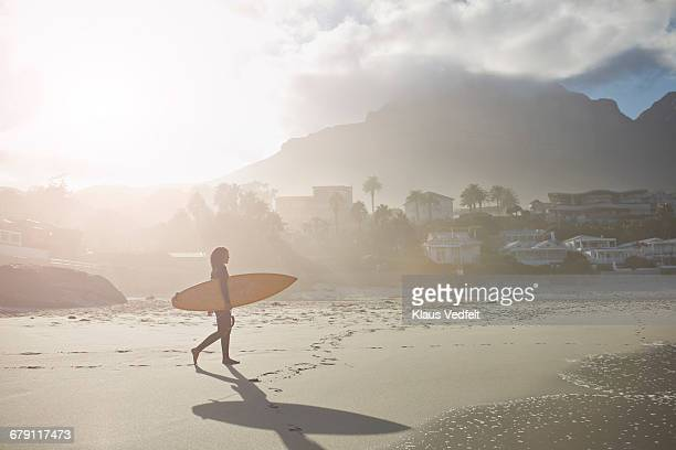Surfer walking on the beach with beautiful sunrise
