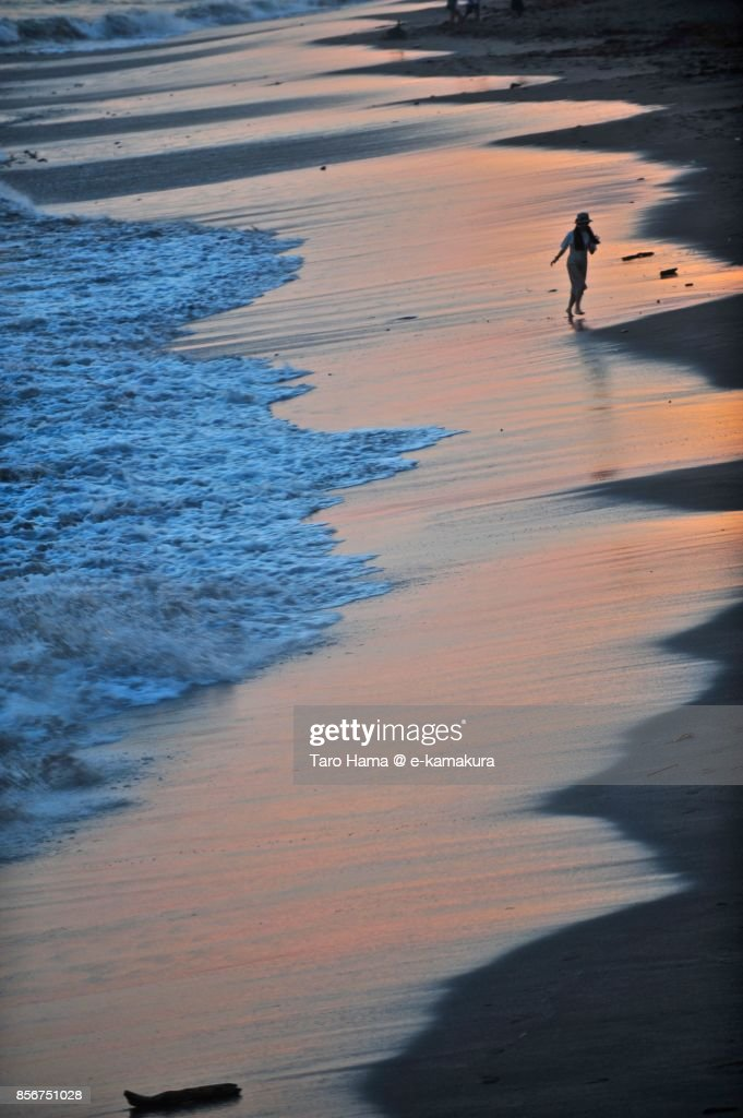 A surfer walking on the sunset beach in Kamakura city in Kanagawa prefecture in Japan : ストックフォト