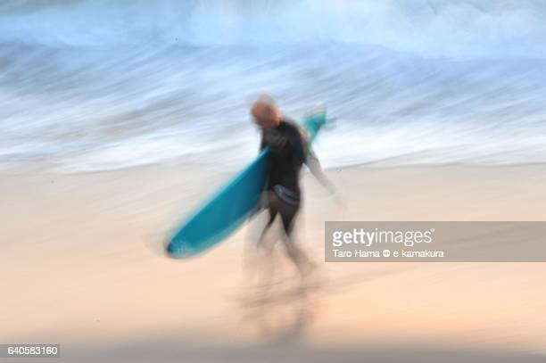 A surfer walking on the sunset beach