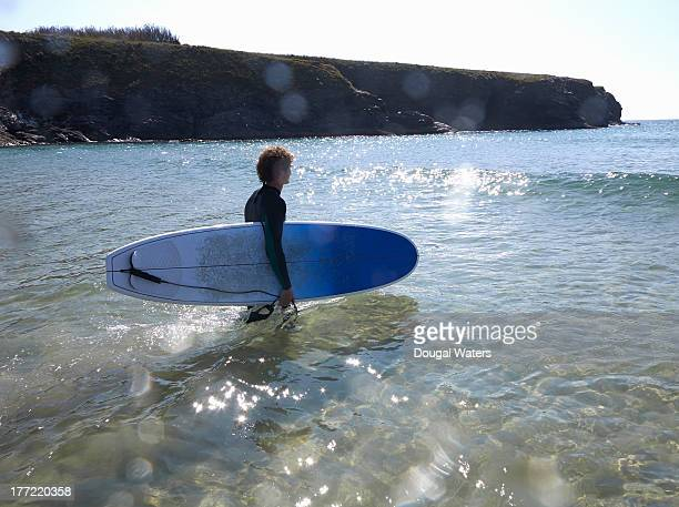 Surfer walking out to sea with board.