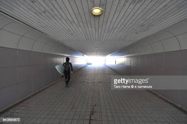 A surfer walking underpass of the road in Japan
