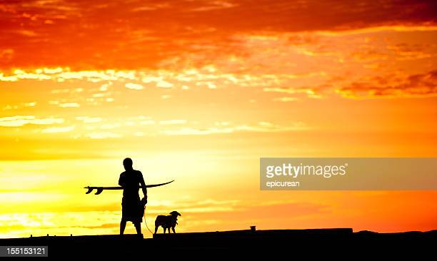 Surfer walking with his board and dog