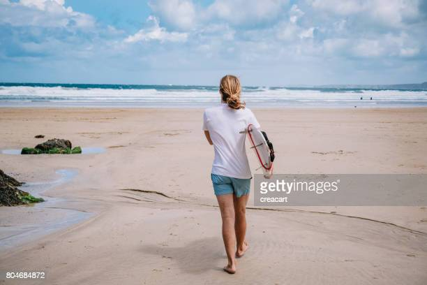 surfer walking with his surfboard, newquay, cornwall. - tee sports equipment stock photos and pictures