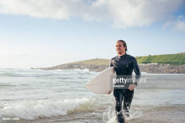 surfer walking with surfboard at fistral beach, newquay, cornwall. - newquay stock pictures, royalty-free photos & images