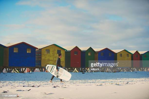 surfer walking with surfboard with colourful beach huts - província do cabo ocidental imagens e fotografias de stock