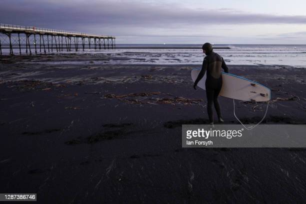 A surfer walks across sea coal deposited on Saltburn beach as he goes for a surf on November 24 2020 in Saltburn By The Sea England Sea coal washes...