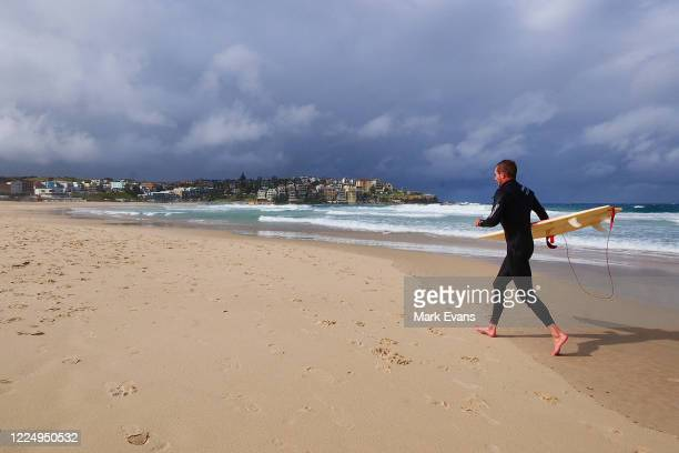 A surfer walks along Bondi beach on May 15 2020 in Sydney Australia Restrictions put in place in response to the COVID19 outbreak have been eased in...