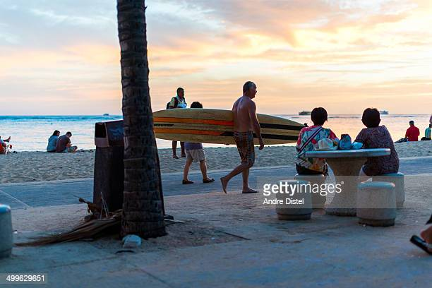 CONTENT] A surfer walks along the shore of Waikiki Beach while tourist and locals watch the sunset