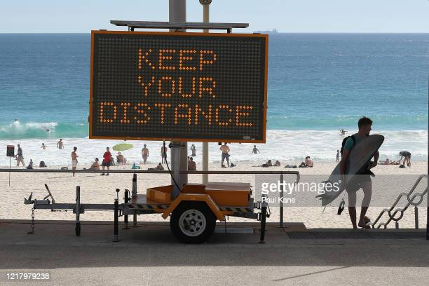 Surfer walks back from the beach past social distancing signage at Scarborough Beach on April 10, 2020 in Perth, Australia. Australians have been...