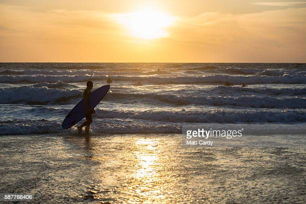 A surfer walks from the sea as the sun sets at Fistral Beach in Newquay on August 9 2016 in Cornwall England From tomorrow the Cornish seaside town...