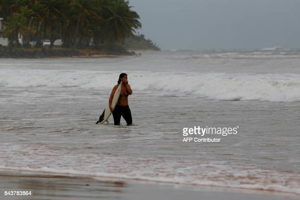 A surfer walks into the ocean in the waters of La Pared Beach in the aftermath of Hurricane Irma in Luquillo on September 7 2017 One of the most...