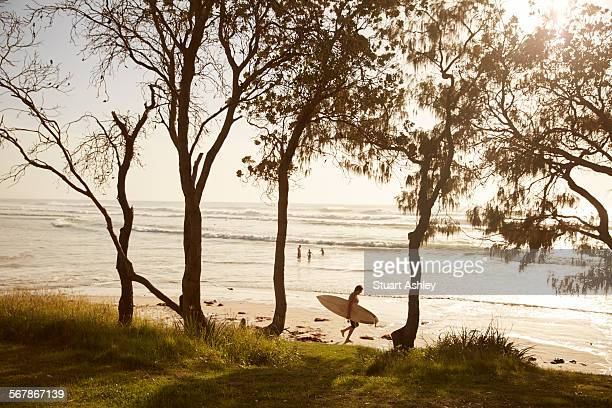 Surfer walks on beach in the early morning