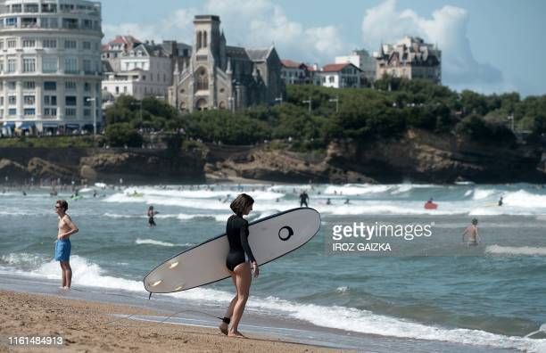 """Surfer walks on the beach as people take a swim on the """"la Grande Plage"""" beach in Biarritz, on August 13, 2019. - The French southwestern seaside..."""