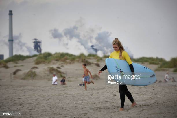 Surfer walks on the beach near the Tata Steel plant on August 21, 2021 in Velsen-Noord. The Tata steel plant is under investigation by the Dutch...