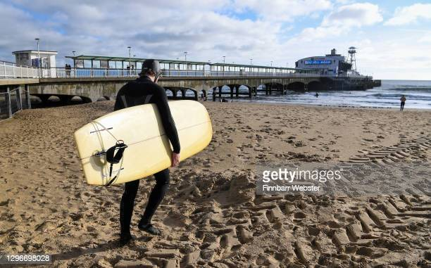 Surfer walks onto the beach on January 16, 2021 in Bournemouth, Dorset. With a surge of covid-19 cases fueled partly by a more infectious variant of...