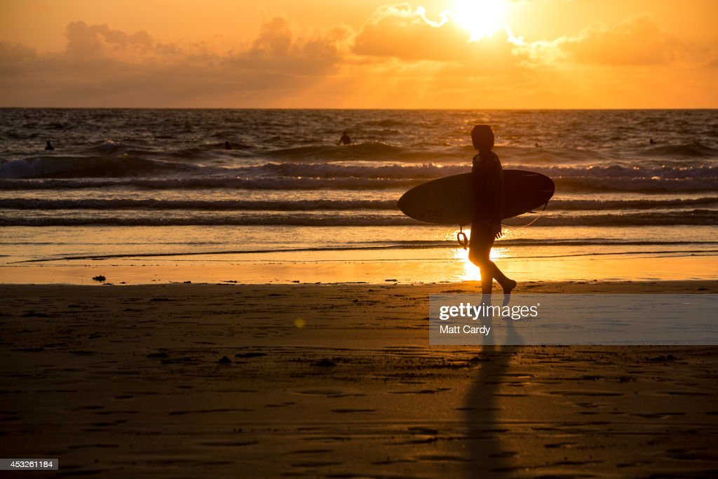 A surfer walks out of the sea as the sun sets on Fistral Beach on the first day of the Boardmasters surf and music festival in Newquay on August 6, 2014 in Cornwall, England. Since 1981, Newquay has been playing host to the Boardmasters surfing competition - which is part of a larger five-day surf, skate and music festival and has become a integral part of the continually popular British surf scene growing from humble beginnings, to one of the biggest events on the British surfing calendar. It now attracts professional surfers from across the globe to compete on the Cornish beach that is seen by many as the birthplace of modern British surfing.