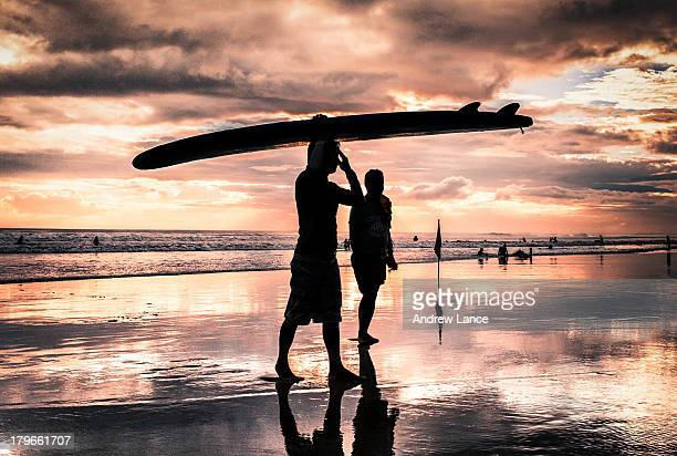 CONTENT] A surfer walks out of the water silhouetted against the sunset on Legian beach Bali Indonesia