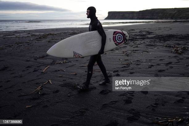 A surfer walks over sea coal deposited on Saltburn beach as he goes for a surf on November 24 2020 in Saltburn By The Sea England Sea coal washes up...