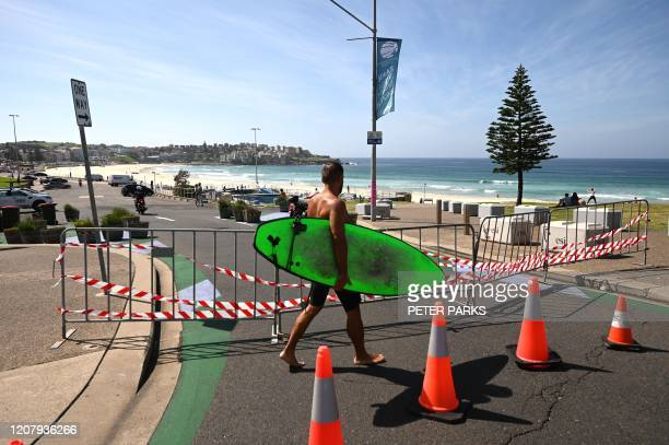 A surfer walks past the entrance to the car park to Bondi Beach which is blocked after authorities closed Sydney's most popular beach on March 22...