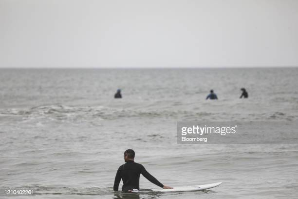 A surfer walks through the water on the beach in Jacksonville Beach Florida US on Saturday April 18 2020 Florida reported a total of 25269 confirmed...