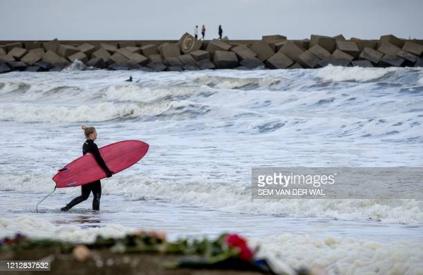 Surfer walks toward the sea at the beach of Scheveningen, northern The Hague, the Netherlands, on May 13, 2020. - Five surfers died after getting...