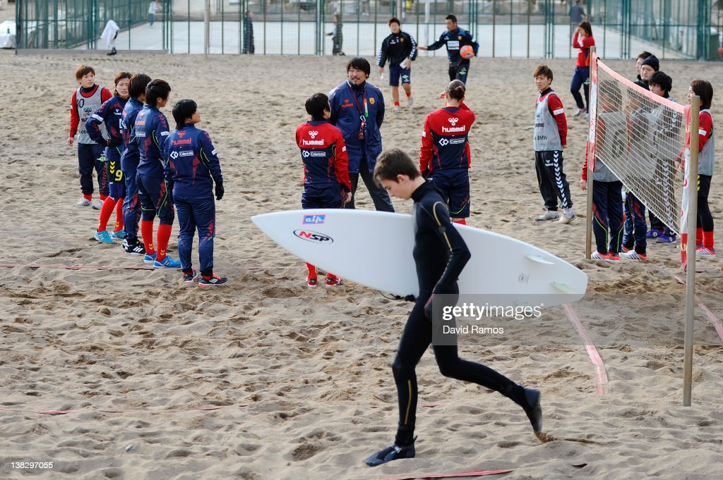 A surfer walks towards the water as IKAN Kobe Leonessa Ladies listen to the Manager Kei Hoshikawa during a training session at the Club Natacion Barcelona sport complex in La Barceloneta beach on February 5, 2012 in Barcelona, Spain.