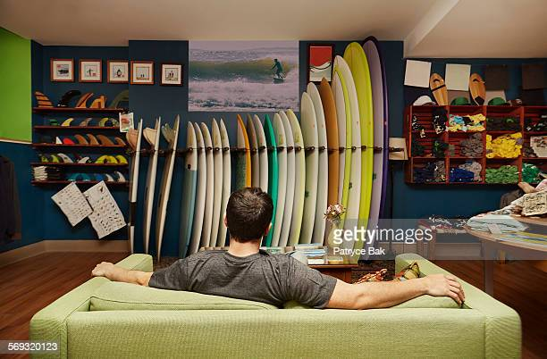 Surfer watches a video at a surf shop.