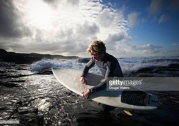 Surfer waxing his board.