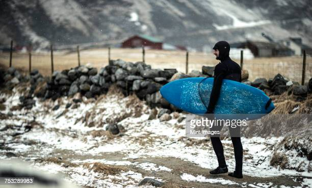 A surfer wearing a wetsuit and carrying a surfboard walking along a snowy beach.