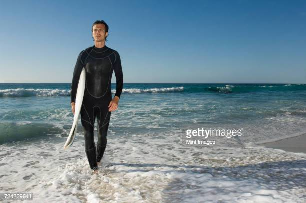 Surfer wearing wetsuit emerging from ocean, carrying surfboard.