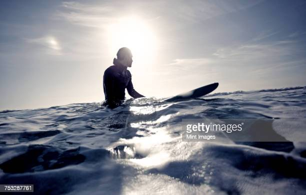 surfer wearing wetsuit sitting on surfboard in the ocean. - surf fotografías e imágenes de stock
