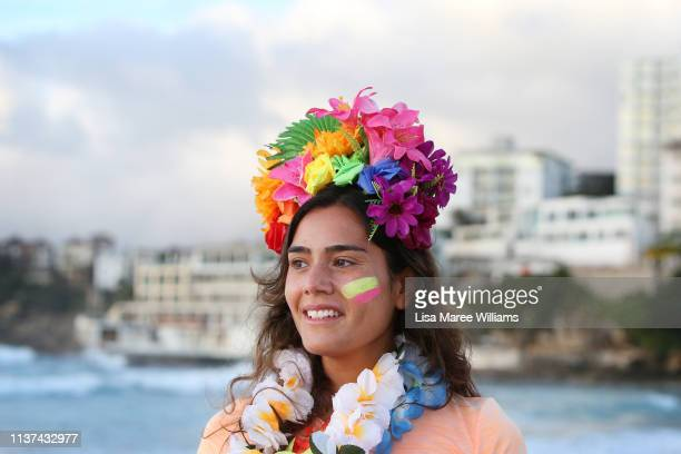 A surfer wears flowers in her hair in solidarity with OneWave at sunrise on Bondi Beach on March 22 2019 in Sydney Australia Surfers gather to...