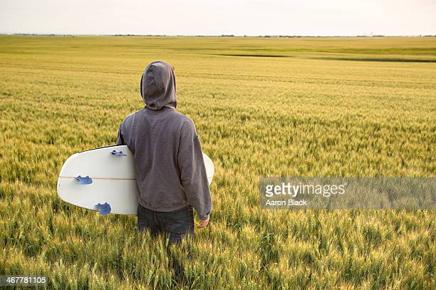 Surfer with a surfboard in an ocean of wheat