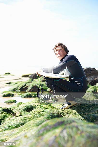 Surfer with board crouching on rock.