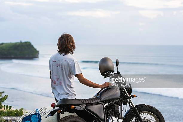 surfer with board on motorcycle