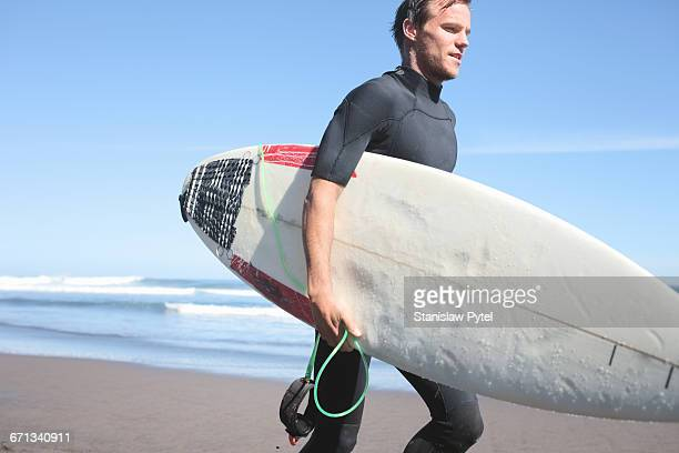 Surfer with board running on beach