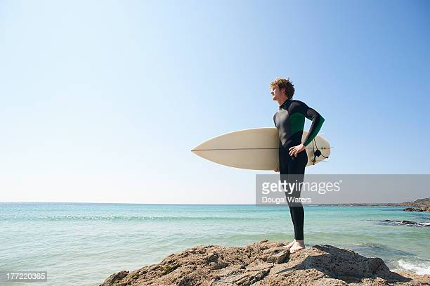 Surfer with board standing on rocks.