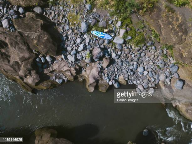 surfer with sup surfboard at river - bedrock stock pictures, royalty-free photos & images