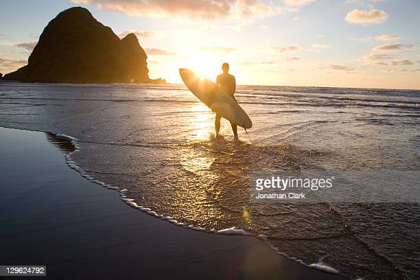surfer with surf board - auckland stock pictures, royalty-free photos & images